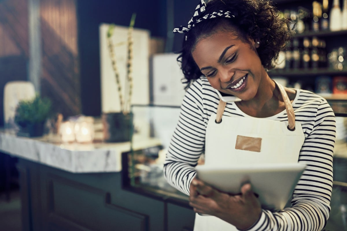 Woman shop owner smiling looking at tablet