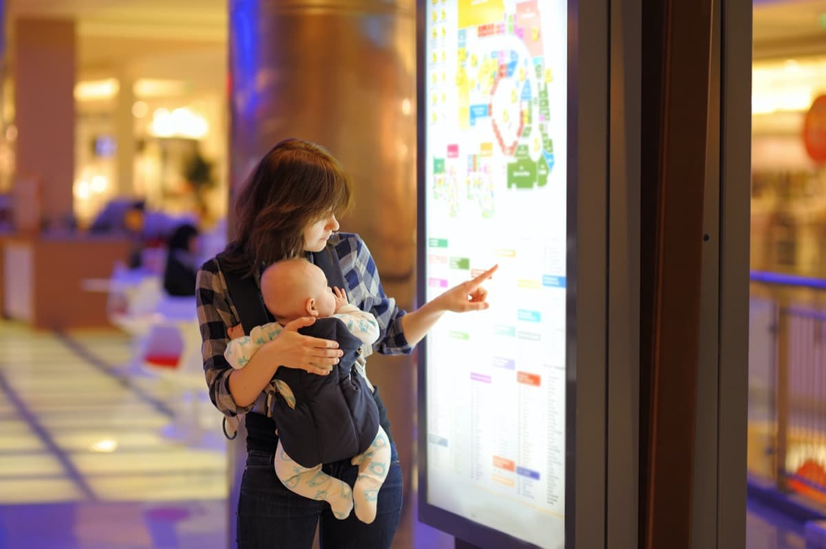 Woman with baby pointing at digital sign