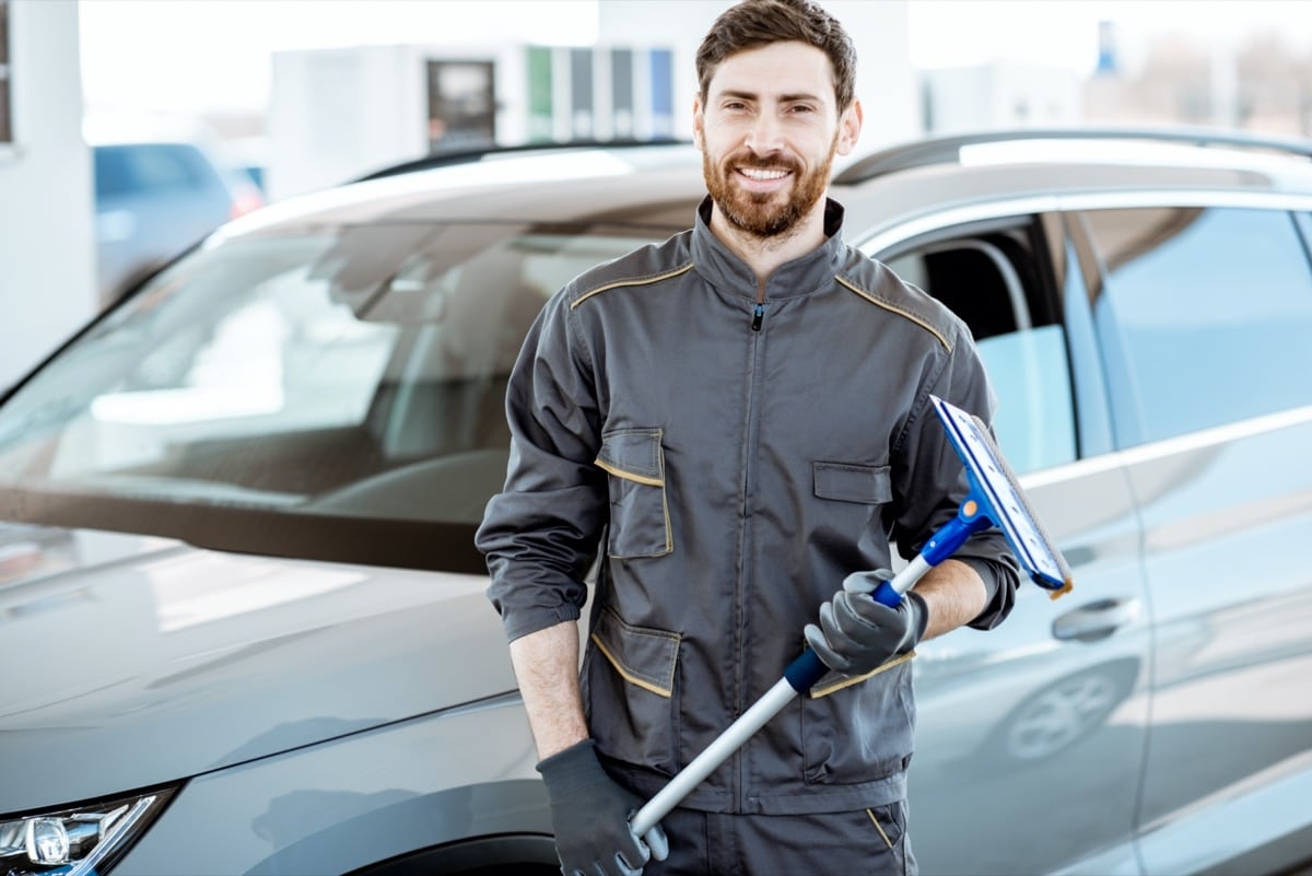 Man standing by car with windscreen wiper